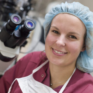 Embryologist sitting by microscope smiling after ICSI | Arizona Reproductive Medicine Specialists