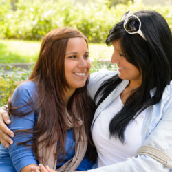 mother | Arizona Reproductive Medicine | Mother and daughter smiling at each other on park bench