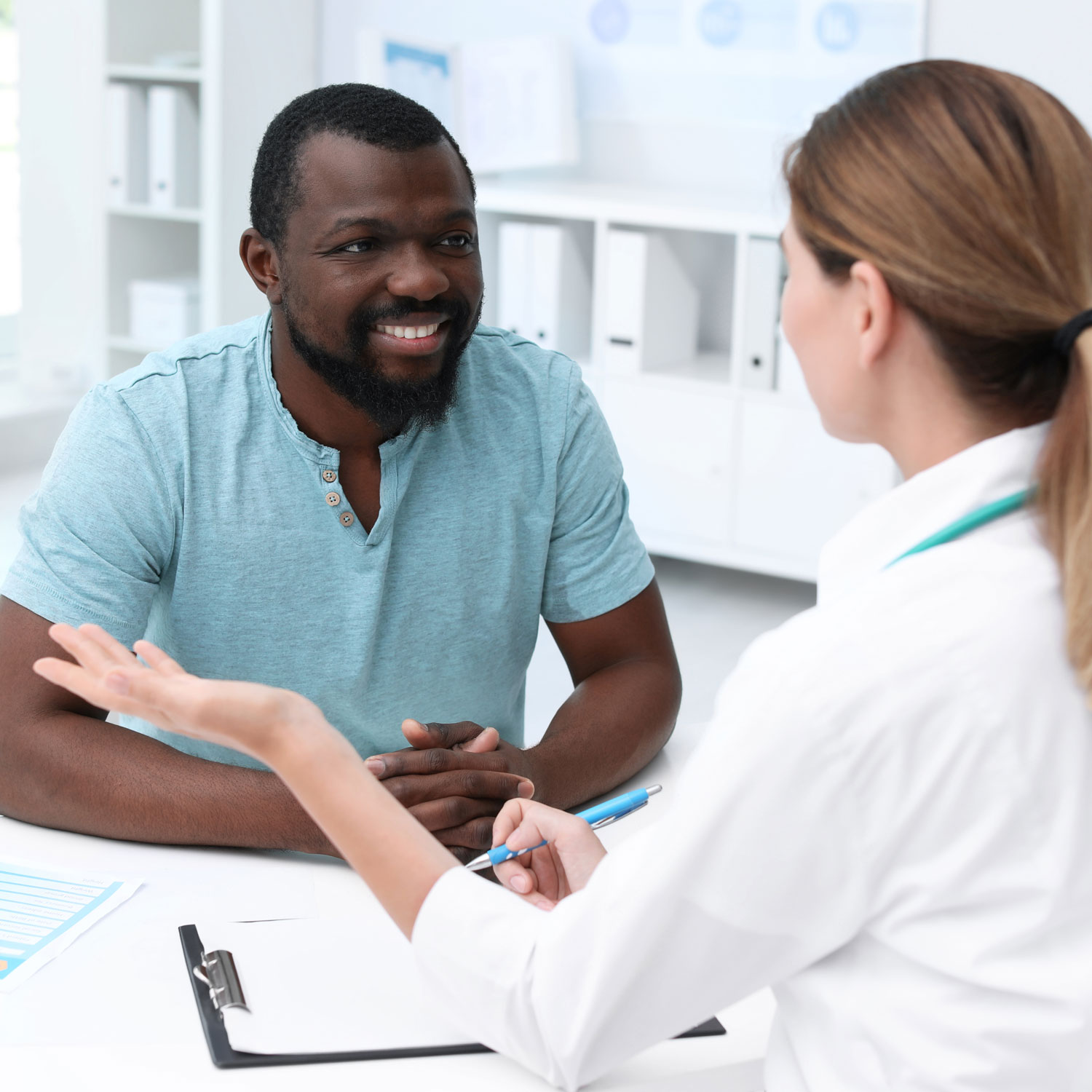 Man in blue shirt talking about treatments for male infertility with his doctor at ARMS | Arizona Reproductive Medicine Specialists